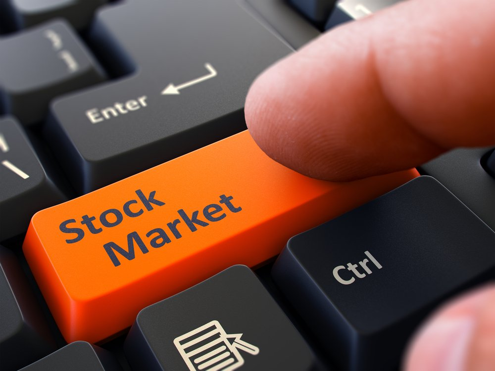 Stock Market Orange Button - Finger Pushing Button of Black Computer Keyboard. Blurred Background. Closeup View.